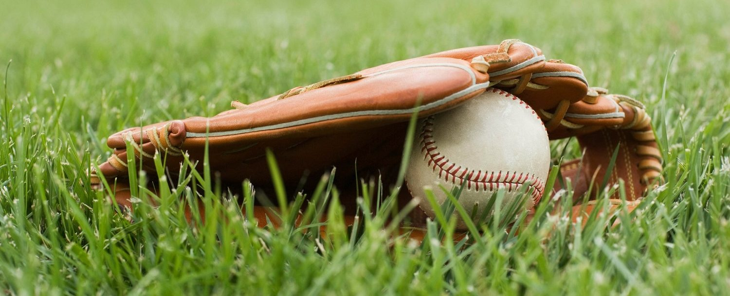 Baseball glove and ball in the grass at Coca-Cola Park