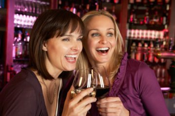 Two Women Enjoying Drink Together In Bar Looking Away From Camera Smiling